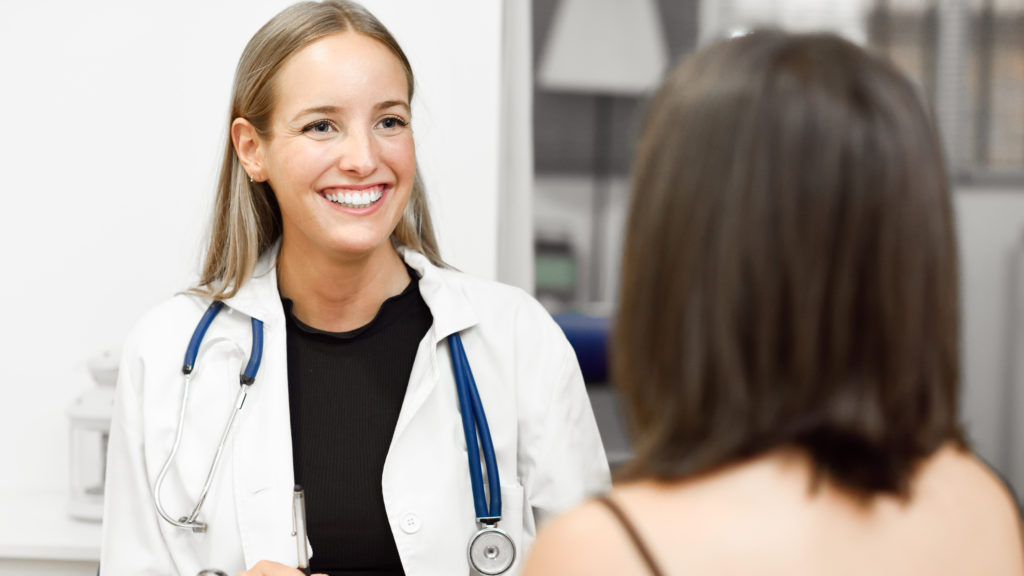 A doctor smiles at a patient knowing there's complete patient price transparency.